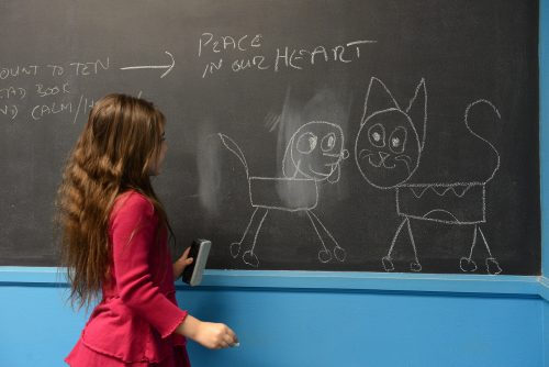 "_Peace in our Heart_ Portrait of young girl Roxie_ she drew a cat and a dog together on a blackboard with chalk, below the inscriptions ""peace in our heart"". author Jonathan Charpentier photography_ Church_ Lifestyle_ Community"