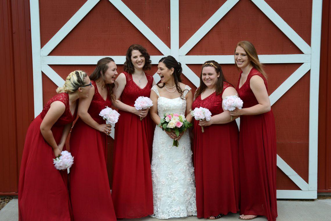 Weddings S&T Shira having fun with bridesmaids in front of red barn door