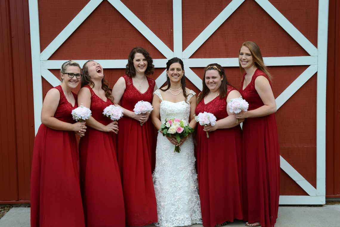 Weddings S&T bridesmaid laughing in front of red barn door